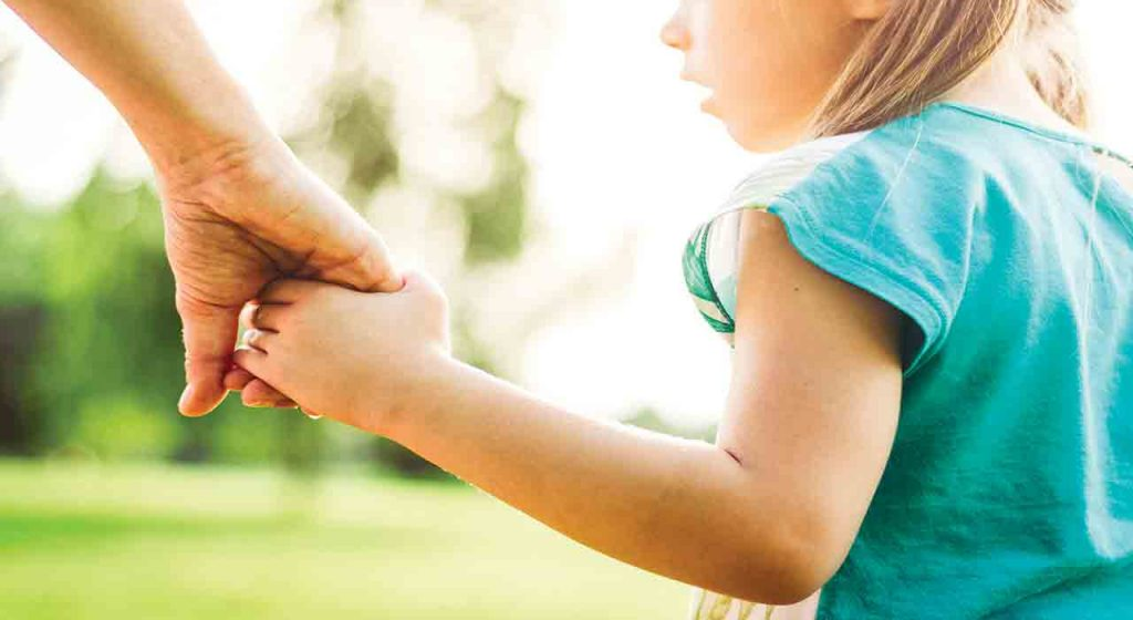 mom holding hands with child