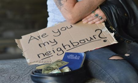 """A beggar holding a sign that says """"Are you my neighbor?"""""""