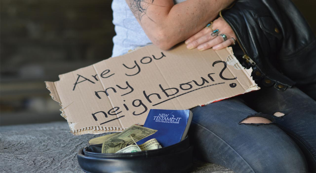 "A beggar holding a sign that says ""Are you my neighbor?"""