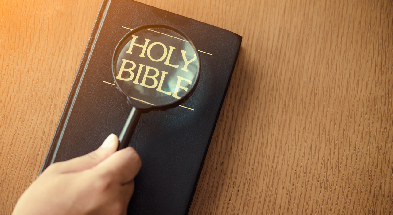A bible being examined with a magnifying glass