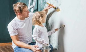 a dad and daughter painting a wall