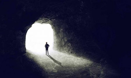 man in dark cave looking into the light