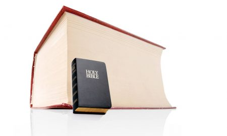small bible next to huge tax code